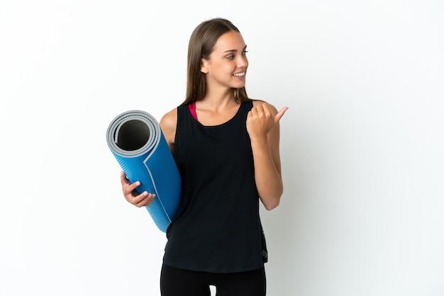 Sportowa kobieta idzie na zajęcia jogi, trzymając matę na białym tle