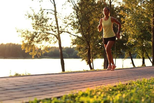 Sportowa kobieta jogger bieganie i trening na zewnątrz w przyrodzie.