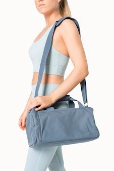 Sportowa kobieta niosąca niebieską torbę sportową, podstawowe wyposażenie siłowni, strzelanie do studia