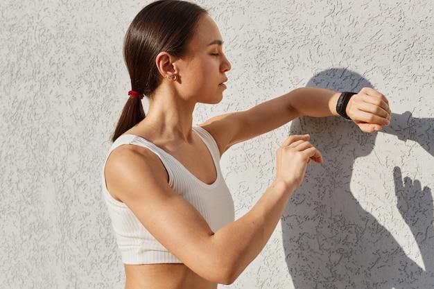 Sportowa kobieta o ciemnych włosach pozuje w pobliżu szarej ściany na świeżym powietrzu i patrzy na zgięcie fitness na dłoni