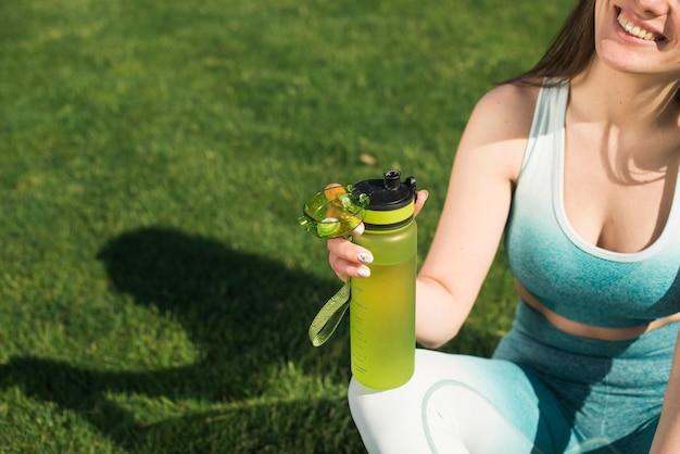 Sportowa kobieta pije izotoniczną wodę