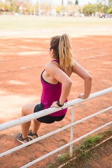 Sportowa kobieta pracuje na torze stadionu