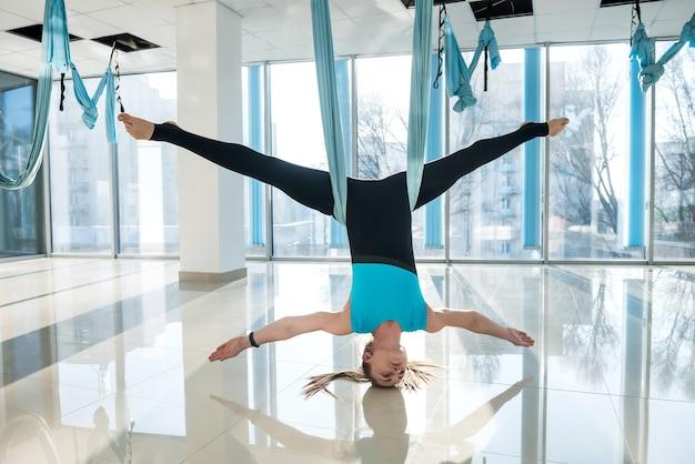 Sportowa kobieta praktykuje jogę latania jako poranne ćwiczenia w siłowni fitness