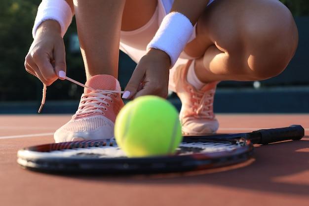 Sportowa kobieta przygotowuje się do gry w tenisa, wiązanie sznurowadeł na świeżym powietrzu.