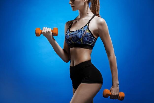 Sportowa kobieta robi ćwiczenia aerobowe z czerwonymi hantlami