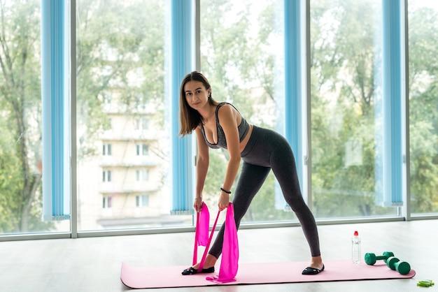 Sportowa kobieta robi ćwiczenia przy użyciu gumowej opaski. koncepcja motywacji.
