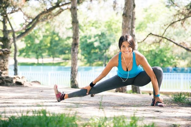 Sportowa kobieta robi ćwiczenia rozciągające w parku