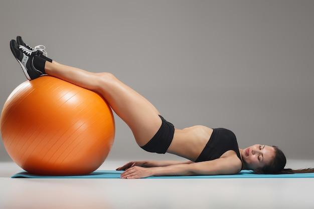 Sportowa kobieta robi ćwiczeniom na fitball