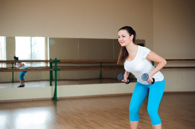 Sportowa kobieta robi ćwiczeniom z dumbbells w gym