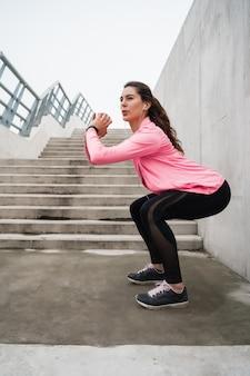 Sportowa kobieta robi ćwiczeniu przy parkiem.