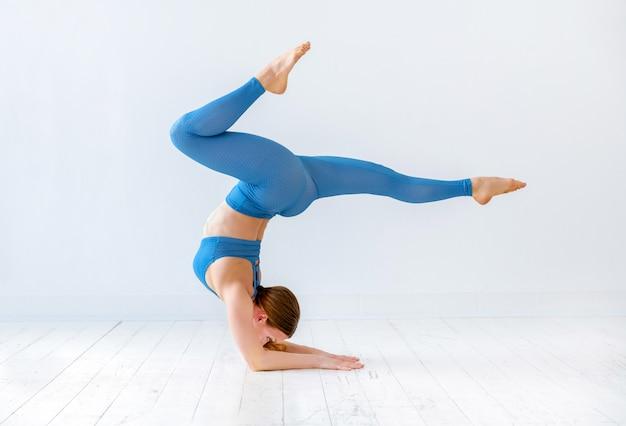 Sportowa kobieta robi łokcia stojaka joga pozie