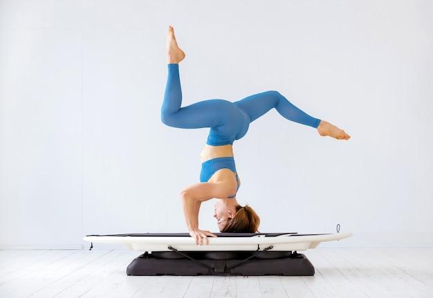 Sportowa kobieta robi stój na głowie na desce surfingowej w widoku z boku z nogami rozłożonymi na białej ścianie w koncepcji zdrowia i fitness