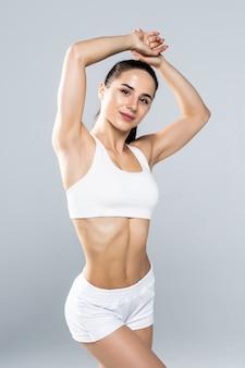 Sportowa kobieta, rozciągając ramiona na białym tle na szarym tle