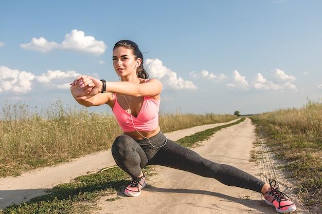 Sportowa kobieta rozciągająca polną ścieżkę