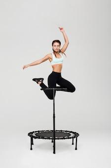 Sportowa kobieta skoki z rękami w górę rebounder z uchwytem