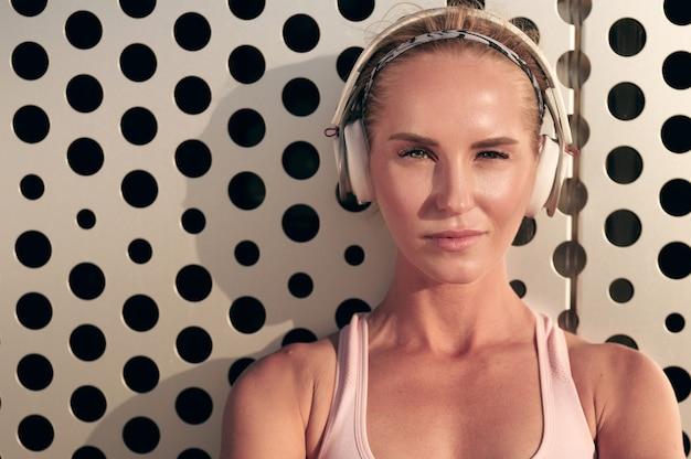 Sportowa kobieta, słuchanie muzyki na słuchawkach