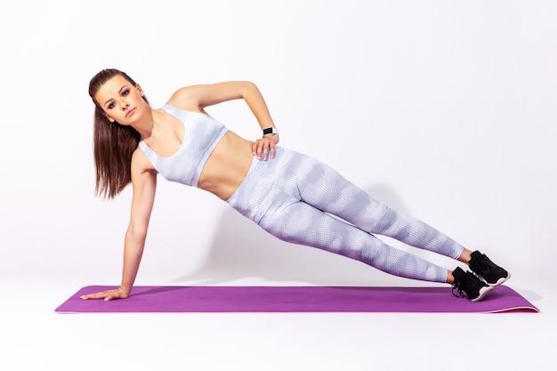 Sportowa kobieta sportowa ćwicząca jogę, wykonująca jedną ręką pozę deski bocznej vasisthasany,