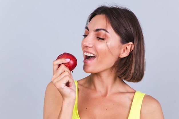 Sportowa kobieta stoi na szarej ścianie, zadowolona z wyników treningu fitness i diety, trzyma wagę, nosi top i legginsy, trzyma jabłko