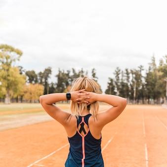 Sportowa kobieta stoi na torze stadionu