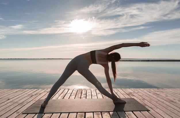 Sportowa kobieta stojąca na plaży wykonuje ćwiczenia jogi.