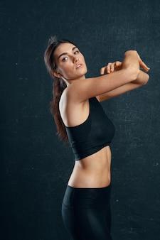 Sportowa kobieta szczupła sylwetka trening ciemne tło