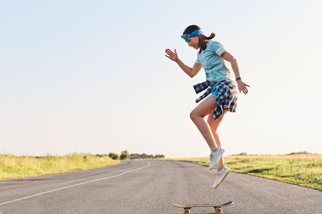 Sportowa kobieta ubrana w t shirt i krótkie robienie sztuczek na deskorolce na ulicy na asfaltowej drodze, skakanie w powietrzu, cieszenie się samotną jazdą na deskorolce o zachodzie słońca w okresie letnim.