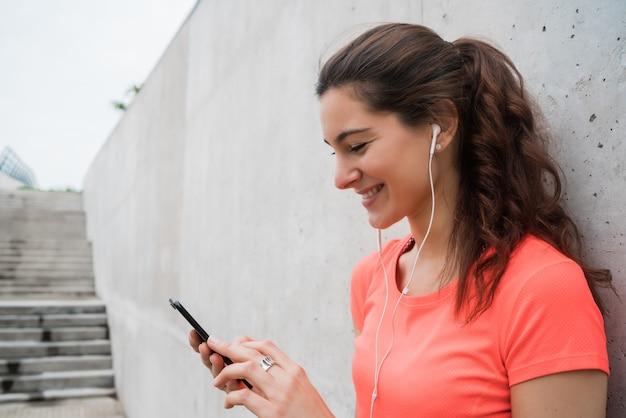 Sportowa kobieta używa jej telefon.