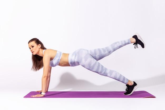 Sportowa kobieta w białych rajstopach i górze, wykonująca ćwiczenia na wysokich deskach i unosząca nogi leżąca na gumowej macie