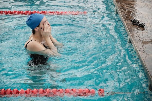 Sportowa kobieta w czapce stojącej w wodzie i tarcie oczu w basenie