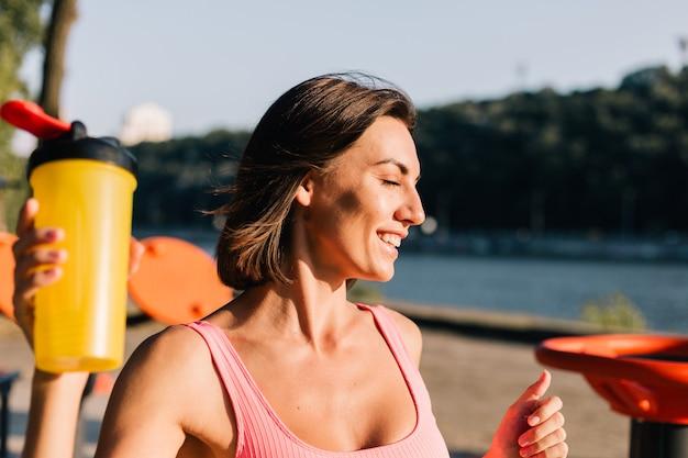 Sportowa kobieta w dopasowanym stroju sportowym o zachodzie słońca na boisku sportowym pozytywnie pozuje ciesząc się letnią pogodą w parku trzymając shaker proteinowy