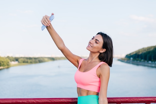 Sportowa kobieta w dopasowanym stroju sportowym o zachodzie słońca na nowoczesnym moście z widokiem na rzekę szczęśliwy pozytywny uśmiech z telefonem komórkowym zrób zdjęcie selfie wideo na historie społeczne