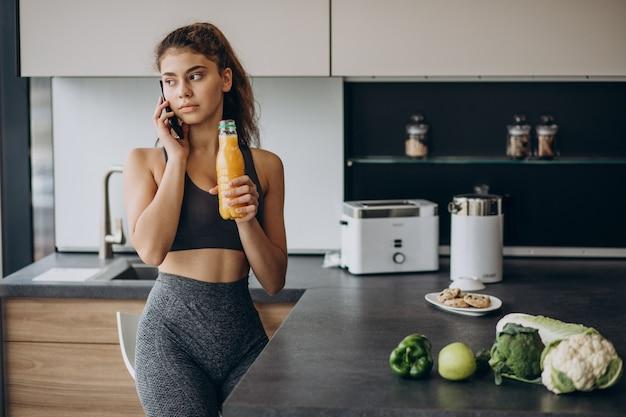 Sportowa kobieta w kuchni przy użyciu telefonu komórkowego