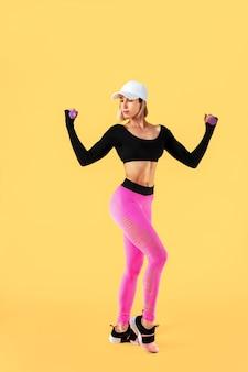 Sportowa kobieta w modnej odzieży sportowej wykonuje ćwiczenia z hantlami. fotografia mięśniowa kobieta na kolor żółty ścianie. siła i motywacja.