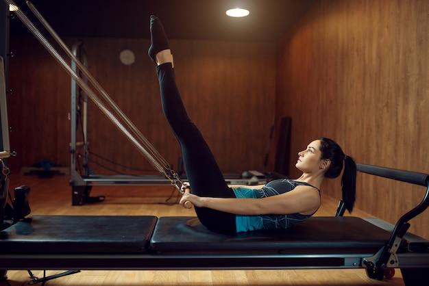 Sportowa kobieta w sprawnej robi ćwiczenia rozciągające pilates w siłowni. trening fitness w klubie sportowym.