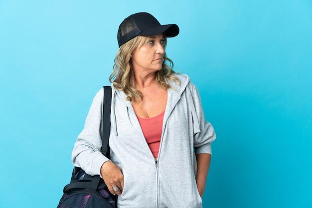 Sportowa kobieta w średnim wieku na odosobnionym tle myślenia