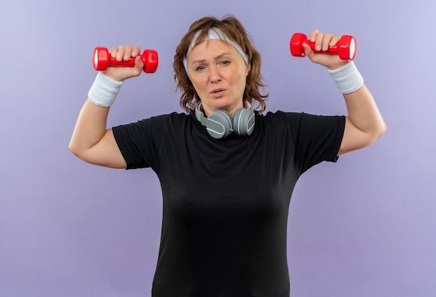 Sportowa kobieta w średnim wieku w czarnej koszulce z opaską, ćwicząca z hantlami, wyglądająca na zmęczoną i wyczerpaną stojącą nad niebieską ścianą