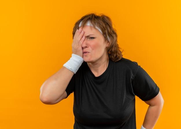 Sportowa kobieta w średnim wieku w czarnej koszulce z opaską na głowie, która zasłania jedno oko ręką stojącą nad pomarańczową ścianą
