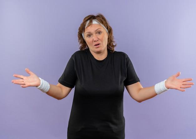 Sportowa kobieta w średnim wieku w czarnej koszulce z opaską, wyglądająca na zdezorientowaną i niepewną, rozłożona na boki i bez odpowiedzi stojąca nad niebieską ścianą