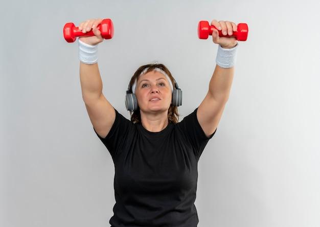 Sportowa kobieta w średnim wieku w czarnej koszulce z pałąkiem na głowę, ćwicząc z dwoma hantlami, patrząc zmęczony stojąc na białej ścianie