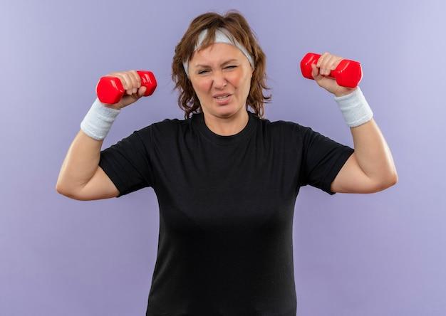 Sportowa kobieta w średnim wieku w czarnej koszulce z pałąkiem na głowę, ćwicząc z dwoma hantlami, patrząc zmęczony stojąc nad niebieską ścianą