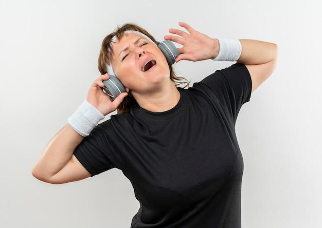 Sportowa kobieta w średnim wieku w czarnej koszulce z pałąkiem na głowę i słuchawkami szalona szczęśliwa słuchająca muzyki stojącej na białej ścianie