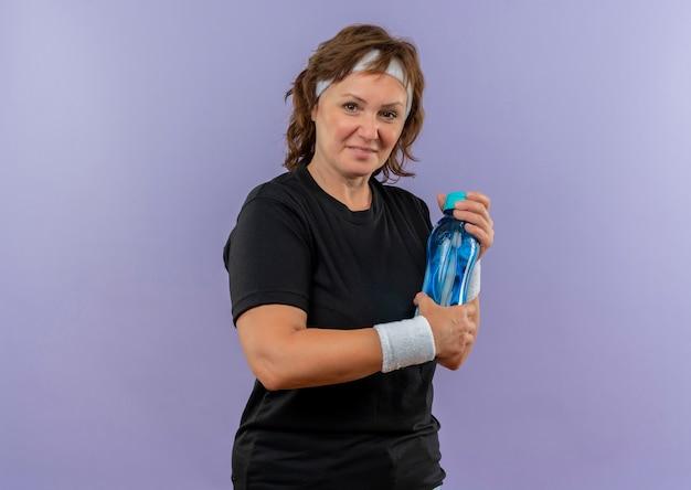 Sportowa kobieta w średnim wieku w czarnej koszulce z pałąkiem na głowę trzymając butelkę wody z uśmiechem na twarzy stojącej nad niebieską ścianą