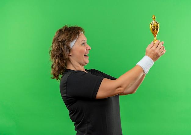 Sportowa kobieta w średnim wieku w czarnej koszulce z pałąkiem na głowę trzymająca trofeum szczęśliwa i podekscytowana stojąca nad zieloną ścianą