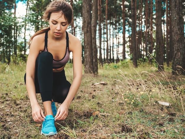 Sportowa kobieta wiążąca sznurowadło na butach do biegania przed treningiem w lesie