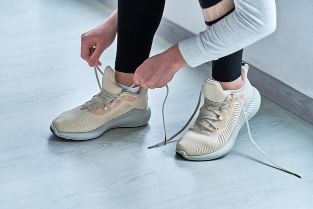Sportowa kobieta wiąże sznurowadła na beżowych wygodnych tenisówkach i przygotowuje się do biegania i biegania. uprawiaj sport i bądź wysportowany. sportowcy ze zdrowym sportowym stylem życia