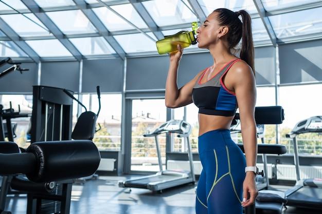 Sportowa kobieta wody pitnej podczas treningu na siłowni