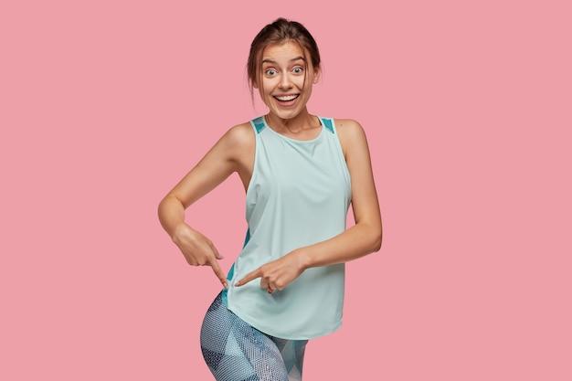 Sportowa kobieta wskazuje na dopasowane pośladki