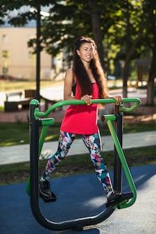 Sportowa kobieta wykonuje ćwiczenia na nogi na symulatorze w parku w słoneczny letni poranek