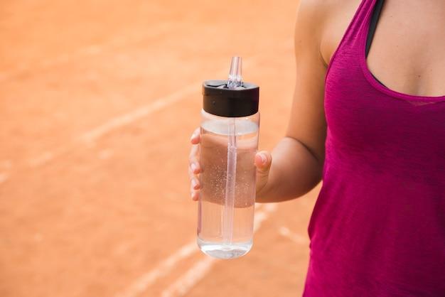 Sportowa kobieta z butelką wody na torze stadionu