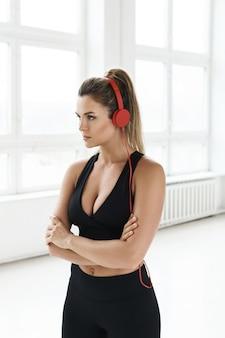 Sportowa kobieta z czerwonymi słuchawkami słucha muzyki motywacyjnej do treningu na siłowni
